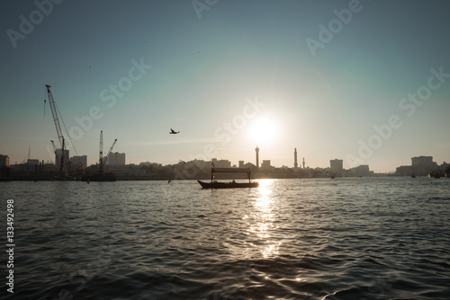 Poster silhouette of a boat floats on the sea channel of Dubai on the background of the