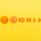 Fototapety Gradual peeling of tangerine on yellow background.