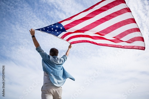 Rear view of man holding american flag on beach