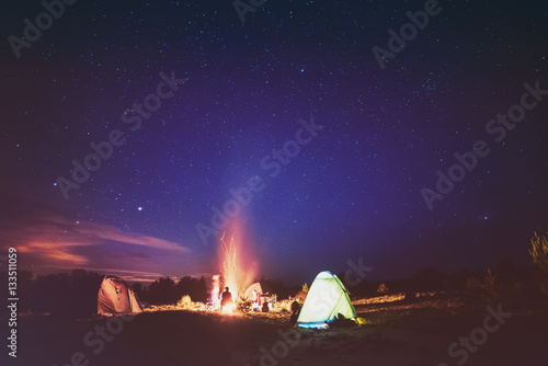 Foto op Canvas Aubergine Camping fire under the amazing blue starry sky with a lot of shining stars and clouds. Travel recreational outdoor activity concept.