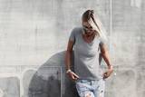 Hipster girl in gray t-shirt over street wall