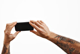Two slightly unfocused mens tattooed arms shows a video on a smartphone on foreground, isolated on white, mockup image