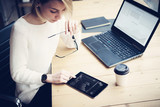 Top view of young beautiful woman working at the wooden table with mobile devices.Female hand touching digital tablet.Graph and diagram on laptop display.Horizontal,blurred background.