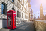 London, England - Traditional red British telephone box with Big Ben and Double Decker bus at the background on a sunny afternoon - 133527815