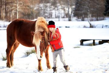Mädchen mit Kaltblutpferd im Schnee