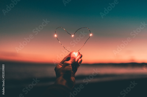 Simbolo del cuore fatto da una striscia di luci led tenuto da una mano di fronte al mare e al cielo in  un tramonto rosso infuocato Poster