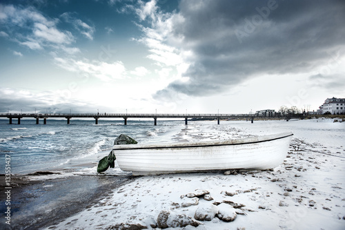 Poster Germany, Usedom, Bansin, Imperial Spa (Kaiserbad): White fishing boat on snowy icy beach with seabridge in the background and dramatic clouds