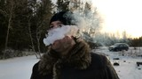 man exhales clouds of white thick smoke outdoors in winter in slow motion
