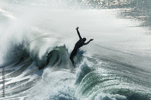 Surfer flails in the air after falling off his board on a wave