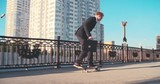 Businessman performing jump on skateboard while riding in city at summer day