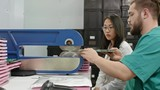 Asian woman helping technician separating PCB material with cutting machine