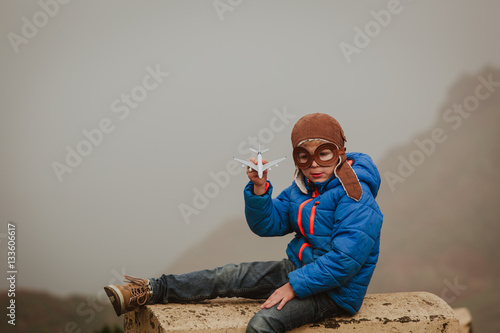 Zdjęcia little boy playint with toy plane in mountains
