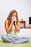 Young woman with allergy problem is sitting in her bed and blowing nose.