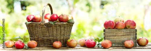 red apples in a basket on wooden table