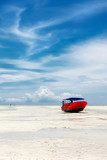 Red boat on the beach of Zanzibar on the blue sky background.