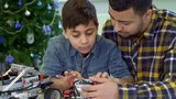 Attractive father and son examining toy tracked ATV. Little brunette boy pressing buttons on the toy console. Young african american man entertaining with his kid at the table