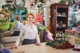 Cheerful woman enjoying work in flower shop