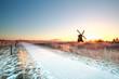 snow on bike path and sun behind windmill