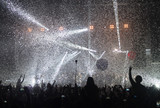 People enjoying good music at rock-concert. Falling of silvery confetti