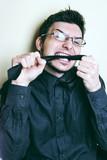 Hombre joven rabioso mordiendo su corbata