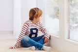 handsome young boy sitting on carpet near the window at rainy day