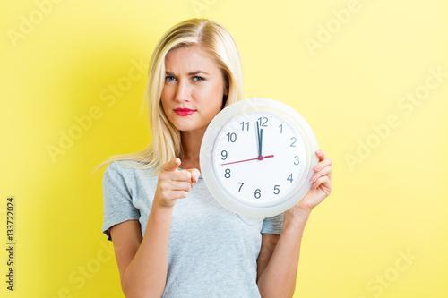 Fotobehang Muziek Woman holding clock showing nearly 12