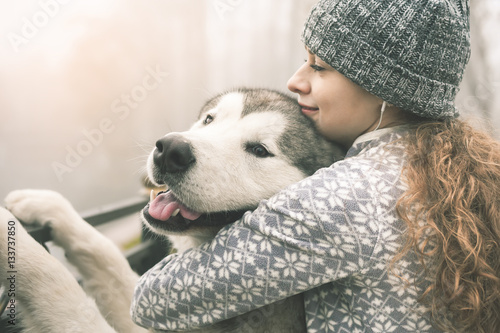 Image of young girl with her dog, alaskan malamute, outdoor Poster