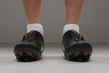 Low view of male legs in cycling boots.