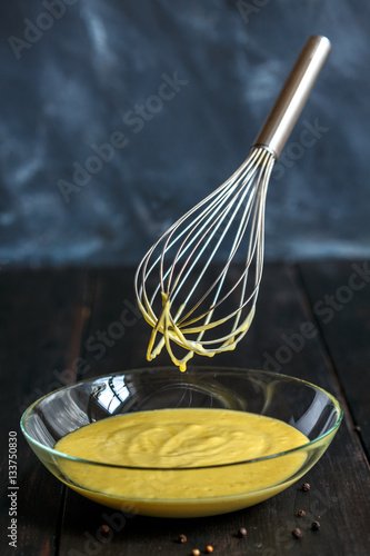 Poster Homemade mayonnaise sauce in a glass bowl and metal whisk.