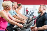 Fototapety Personal trainer instructs senior woman about spinning at the gym