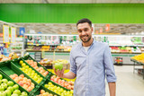 happy man buying green apples at grocery store