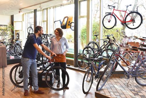 Poster Fahrradgeschäft: Verkäufer und Kundin beim Verkaufsgespräch // bike shop