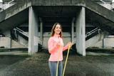 Cheerful sporty woman doing biceps hammer curl exercise with fitness resistance band. Urban outdoor workout.