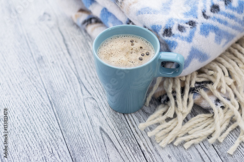 Poster Warm plaid with blue pattern and blue cup of coffee on grey wooden background