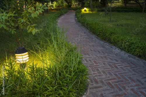 Poster Twilight garden scene with lamp and brick curved road