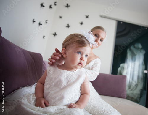 d470cbc1505 Beautiful bride with her little daughter. Summer wedding and baptism. Cute baby  girl with