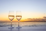 Fototapety Pair of wine glasses on a bar at sunset.