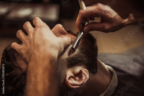 Men barber shaves his beard. Plakat