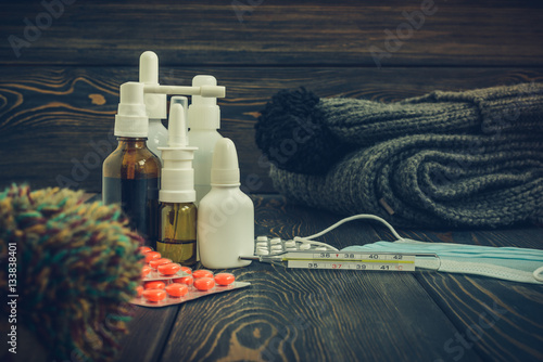 Poster Medication tablets from illness and influenza on a rustic wooden background with woolen scarf  cap
