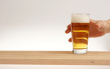 Hand take glass of light beer from wooden board.