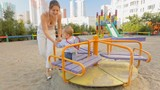 Happy young mother spinning her baby son on the carousel at playground