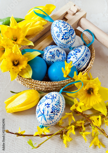 Poster Traditional Czech easter decoration - regional wooden ratchet instrument with painted blue eggs with daffodils and tulips flower in the basket