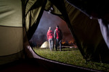View from inside a tent on the couple hikers at night camping with a smoke after campfire. They enjoy the view of beautiful mighty mountains and night lights of the town