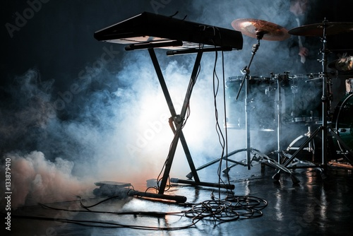 Poster Electric piano and drum kit in dark smoky studio