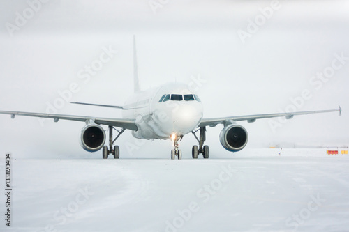 Zdjęcia Taxiing passenger airplane in a snow blizzard