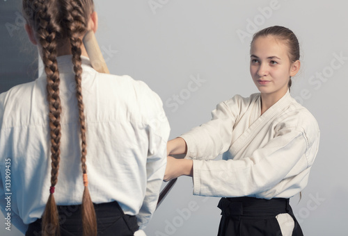 Two girls practice sword on Aikido training on white background Poster