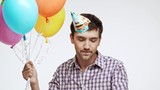 Active young Caucasian male with dark hair and light bristle dancing on white background wearing birthday cap and multicolored balloons