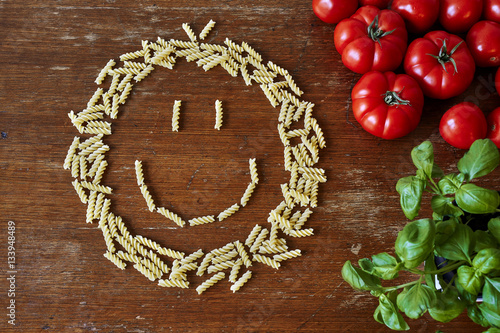 a bunch of pasta tomatoes and herbs giving space Poster