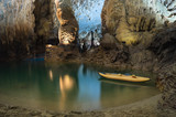 River and rock cliff, and rowing tourist boat inside of Phong Nha Cave in Phong Nha-Ke Bang National Park, a UNESCO World Heritage Site in Quang Binh Province, Vietnam
