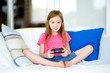Funny little preteen girl playing with game console